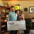 The Heckert's receiving a check to help adopt a girl with DS